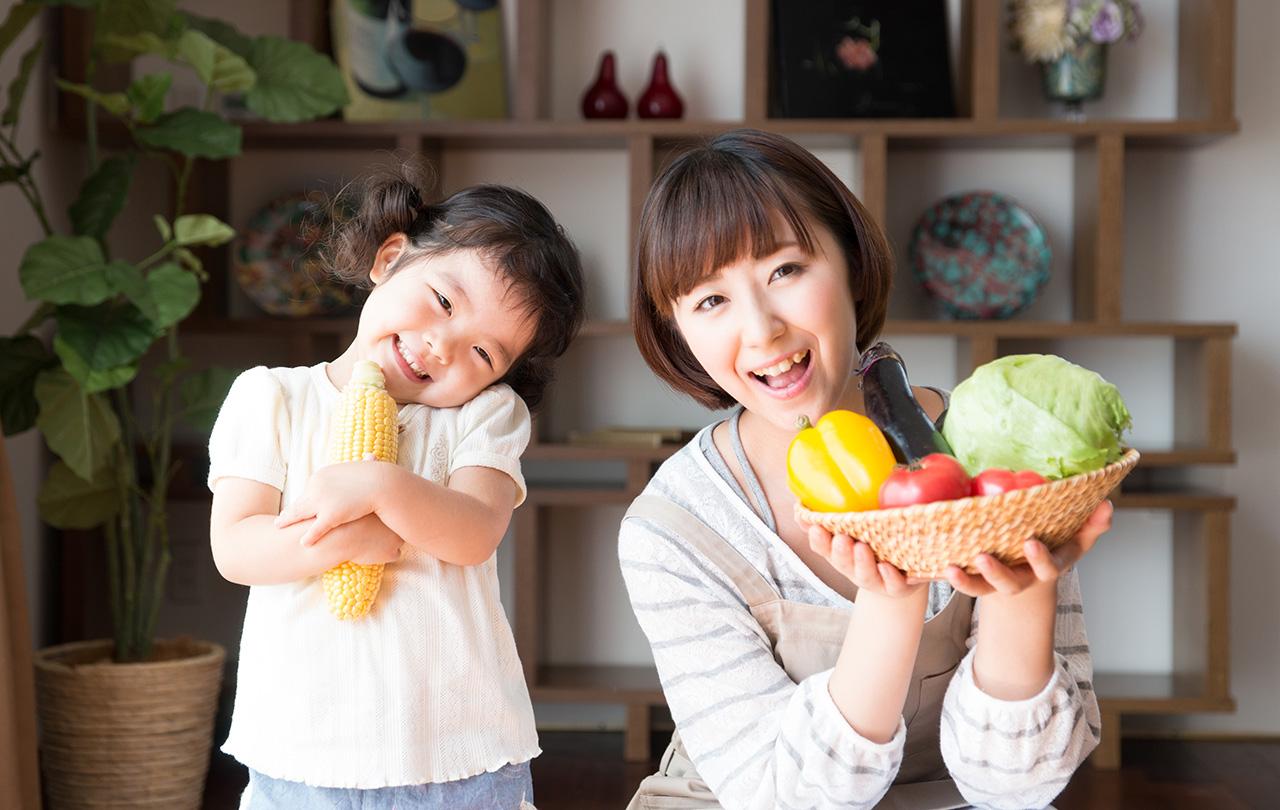 無添加野菜(有機野菜)を持つ笑顔の母娘